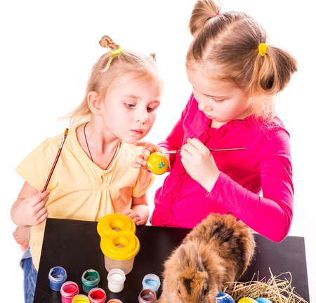 Two happy kids painting easter eggs isolated on white. Happy Easter photo