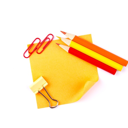 Orange sticky paper note with red clips and pencils isolated on white photo