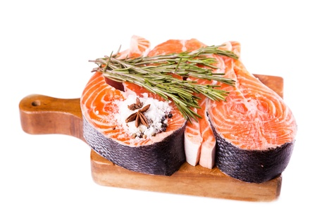 Raw salmon steak with rosemary isolated on white photo