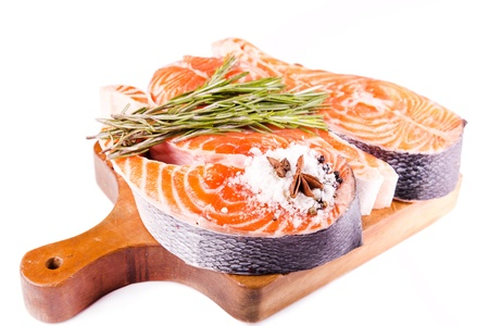 Raw salmon steak with rosemary on a wooden board isolated on white photo