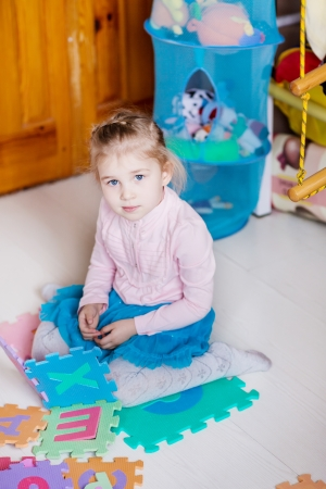 Cute little girl playing puzzles on the floor photo