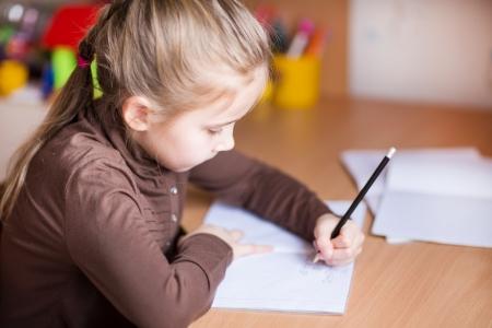 Roztomilá holčička začala psát domácí úkoly u stolu Reklamní fotografie - 18204092