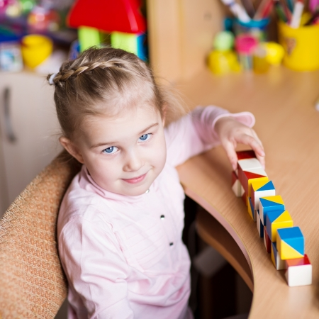 Cute little girl playing with blocks at the table photo