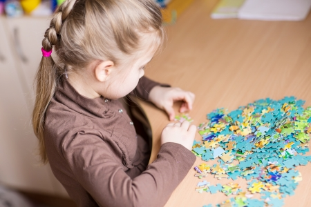 Cute little girl playing puzzles at the table photo