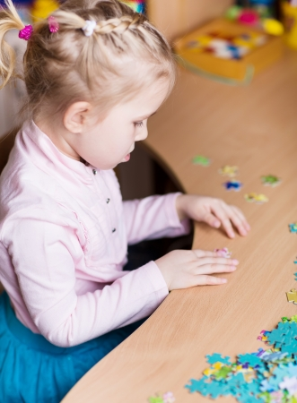 Cute little girl playing puzzles at the table