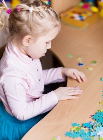 Roztomilá holčička hraje hádanky u stolu