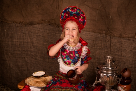 Beautiful russian girl drinking tea and eating pancakes photo