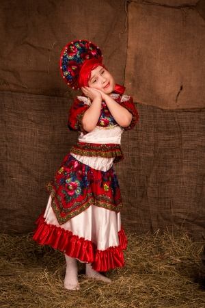 Beautiful little girl in national costume dancing photo