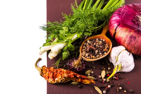 Vaus spices and herbs, onion and garlik on a brown tablecloth with copyspace for you text Stock Photo - 18518340