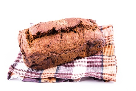 Fresh  homemade brown bread with cereals on a kitchen towel isolated over white