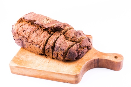 Fresh  sliced homemade whole grain brown bread with cereals on a wooden board isolated on white photo