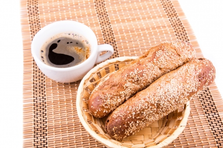 Freshly baked bread rolls with sesame with cup of coffee served on a serviette isolated on white photo