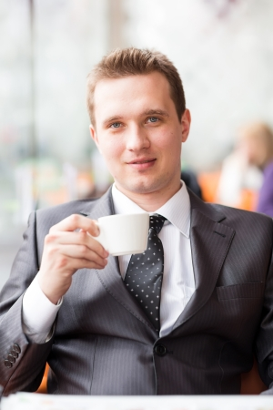 Young handsome businessman sitting in a cafe drinking coffee photo