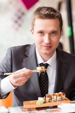 sushi menu: Young handsome businessman eating sushi with sticks in a cafe Stock Photo