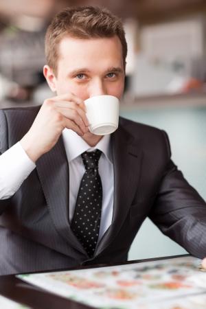 Mladý pohledný podnikatel sedí v kavárně pití kávy Reklamní fotografie