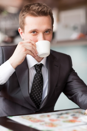 Young handsome businessman sitting in a cafe drinking coffee Stock Photo