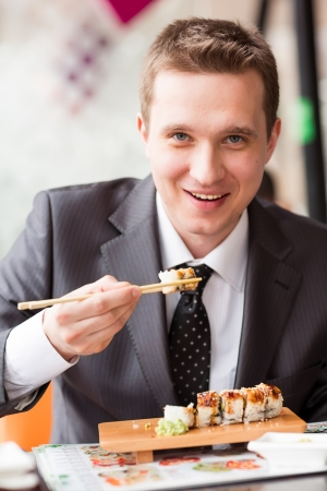 Young handsome businessman eating sushi with sticks in a cafe Stock Photo