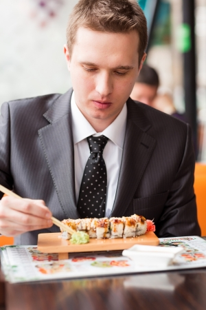 Young handsome businessman eating sushi with sticks in a cafe photo