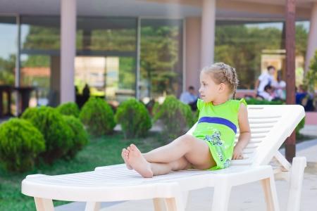 Krásná holčička odpočívá na salonku u hotelového bazénu na dovolenou