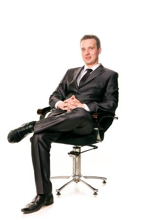 Jistý usmívající se mladý podnikatel sedí na židli, izolovaných na bílém