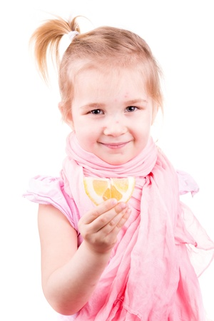 Sick little girl with chickenpox eating lemon isolated on white photo