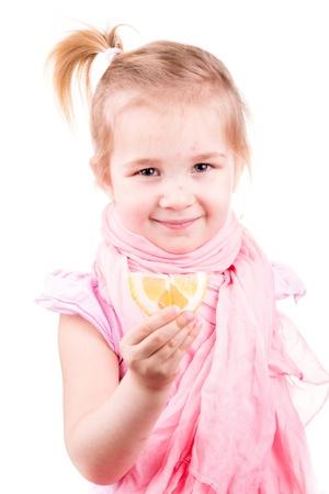 Sick little girl with chickenpox eating lemon isolated on white Reklamní fotografie