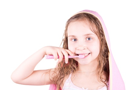 Beautiful happy smiling little girl brushing her teeth after bath, shower isolated on white photo