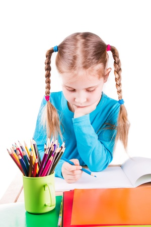 Adorable little girl drawing a picture in a sketchbook with colored pencils isolated on white photo