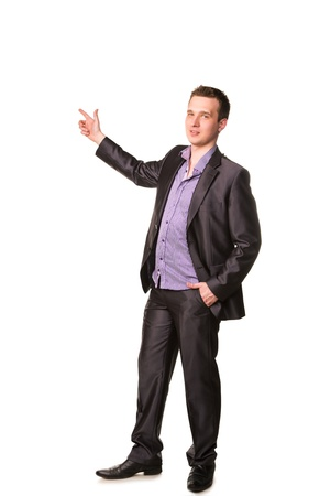 Happy young friendly smiling businessman pointing finger isolated on white photo