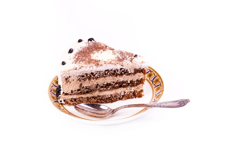 A piece of tasty coffee chocolate cake on a plate with a spoon isolated on white photo