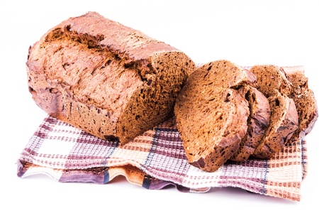 Fresh sliced homemade brown bread with cereals on a kitchen towel isolated over white