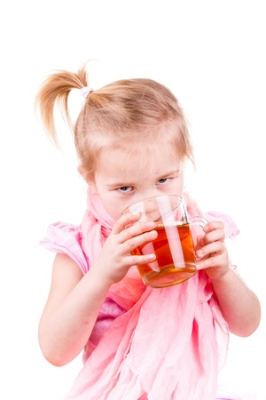 Sick little girl with chickenpox drinking tea with lemon isolated on white photo