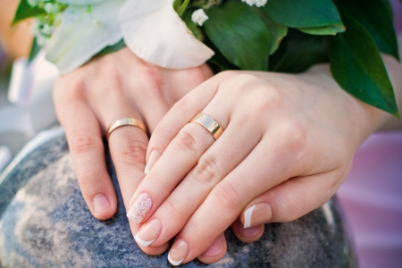beautiful bride: Hands of bride and groom and rings with wedding bouquet on background