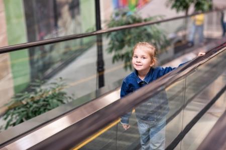 Roztomilé dítě v nákupním centru, stojící na pohyblivých schodech, eskalátor Reklamní fotografie