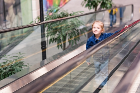 Cute little child in shopping center standing on moving staircase, escalator photo