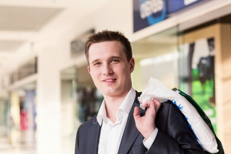 Attractive young man shopping with bags at the store photo