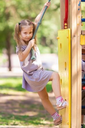 Krásná holčička na venkovním hřišti v létě Reklamní fotografie