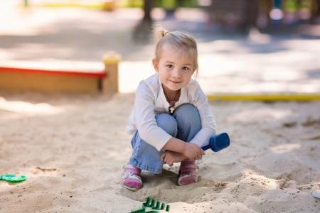 Šťastné holčička hraje v sendbox na hřišti Reklamní fotografie