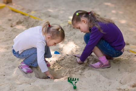 sandpit: Happy little girls playing in a sendbox on the playground