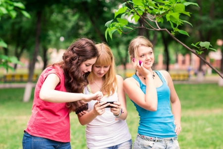 Group Of happy smiling Teenage Students outdoor Using Mobile Phone photo