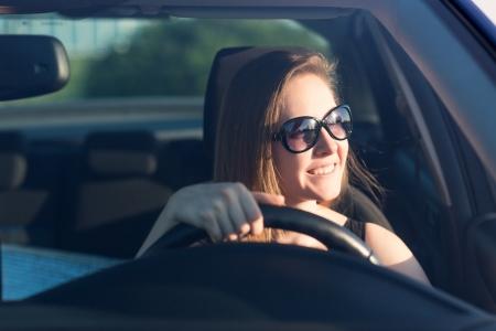 Krásné podnikatelka v brýlích řídí její auto