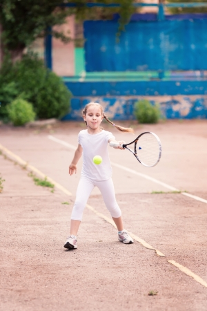 Adorable little child playing tennis with racket and a ball on tennis court photo