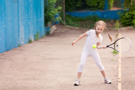 Adorable little child playing tennis with racket and a ball on tennis court