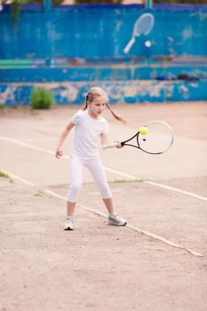 Roztomilé malé dítě hrát tenis s raketou a míček na tenisový kurt