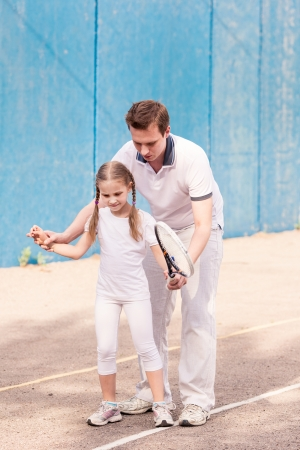 Instructor teaching a child how to play tennis on a court outdoor Stock Photo