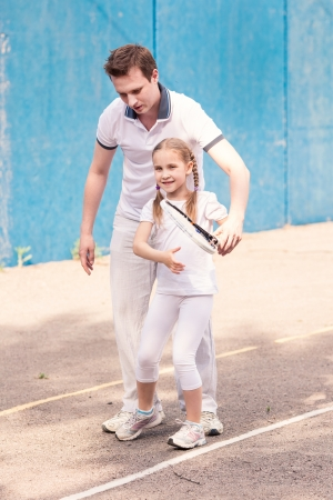 Instructor teaching a child how to play tennis on a court outdoor photo