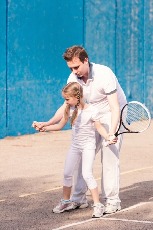 Instructor teaching a child how to play tennis on a court outdoor Reklamní fotografie