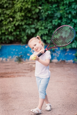 kid  playing: Adorable little child playing tennis with racket and a ball on tennis court