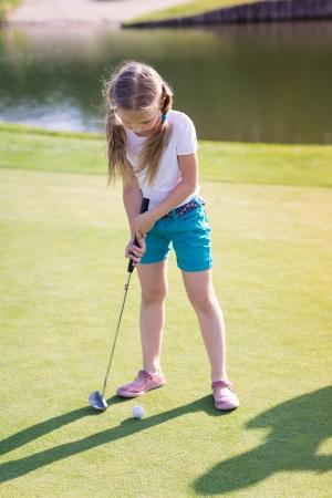 Roztomilá holčička hrát golf na poli venkovní