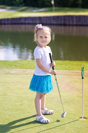 Cute little girl playing golf on a field outdoor photo